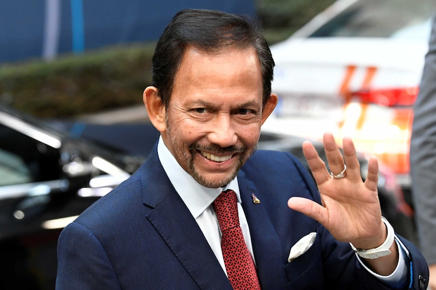 Sultan of Brunei Hassanal Bolkiah waves to a crowd, wearing a suit and tie.
