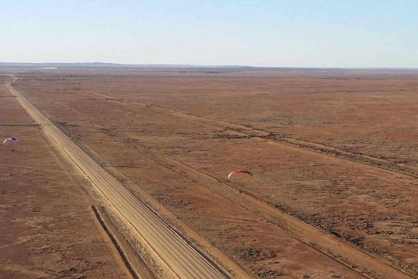 Three people can be seen paragliding across dry Australian terrain.