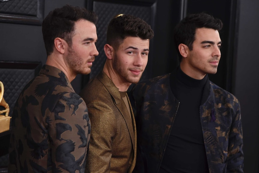The Jonas brothers stand on the Grammys red carpet
