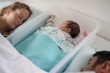 A baby sleeps inside a clear plastic tub with a man and woman on either side. they're all in the bed.