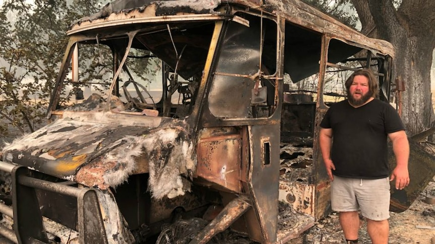 A young, bearded, long-haired man in a black shirt and shorts stands next to a burnt-out bus.