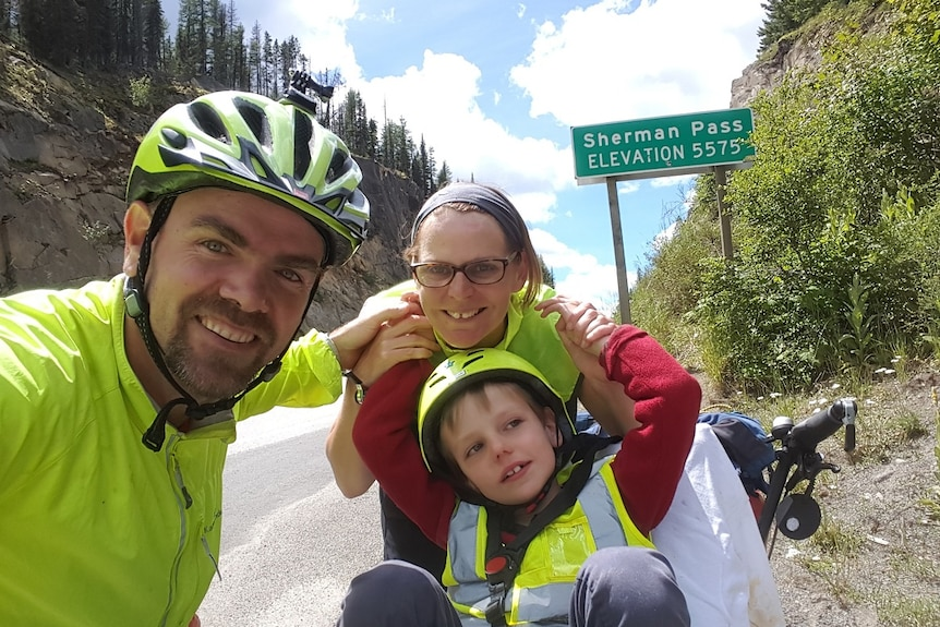 Fiona Churchman, Travis Saunders and their son Patch in front of a road sign saying Sherman Pass
