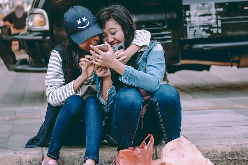 Two women sitting on the pavement with their arms around each other
