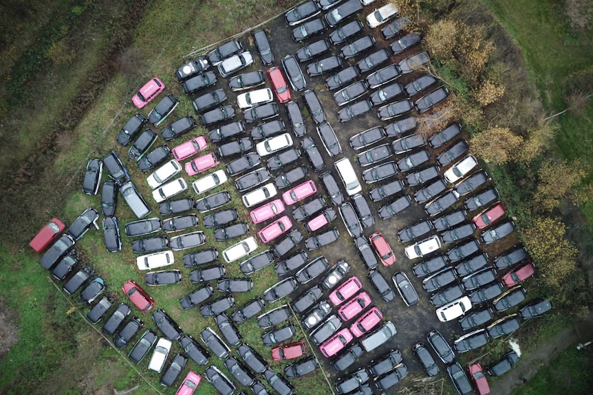 An aerial top-down view of a field of disused taxis outside of London.