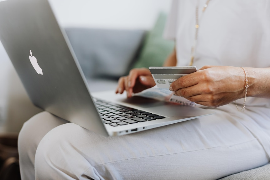 A brown woman wearing white jeans and a white top sits down with a laptop in one hand and a bank card in the other.
