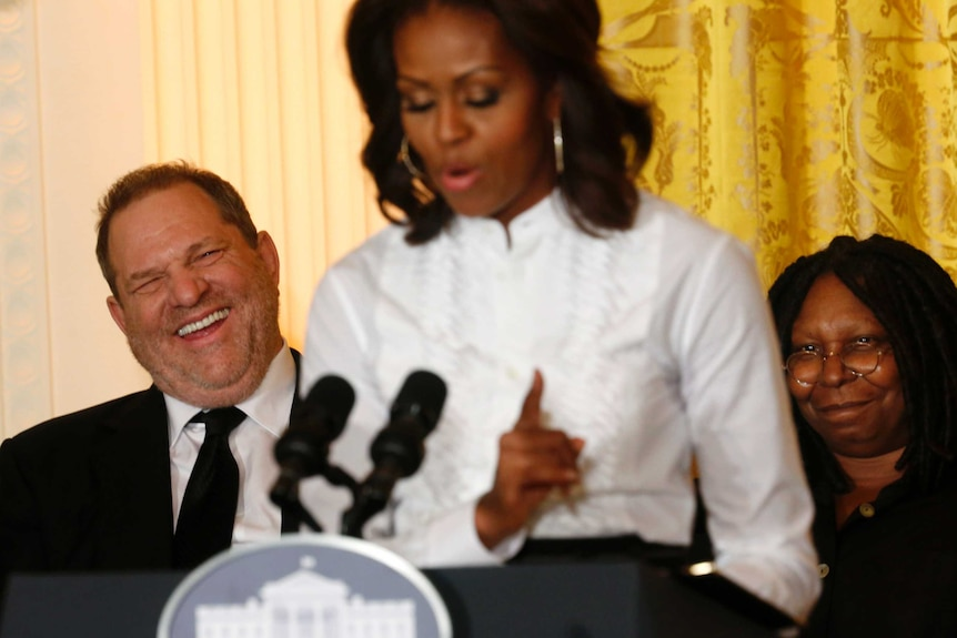 In-focus Harvey Weinstein laughs while sitting behind an out-of-focus Michelle Obama.