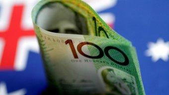 An Australian $100  note is seen with Australian flag behind