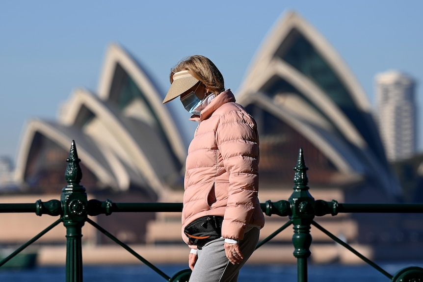 A woman in a pink jacket and peak hat wears a mask with her face in shadow in front of the Sydney Opera House