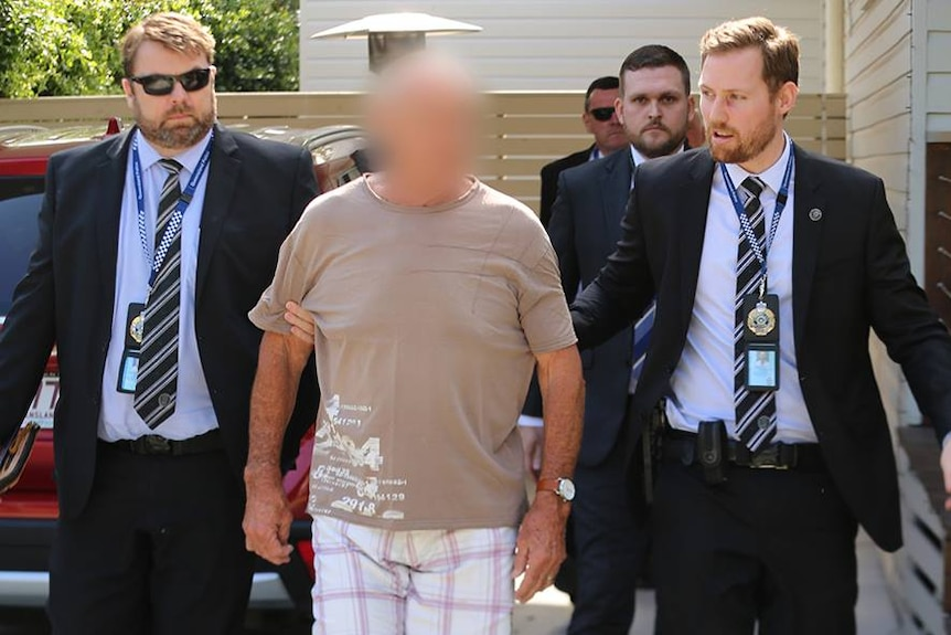 A man being led by three police officers