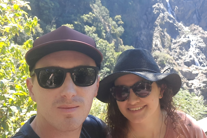 james and emma standing next to each other, wearing sunglasses and hats, with a valley behind them