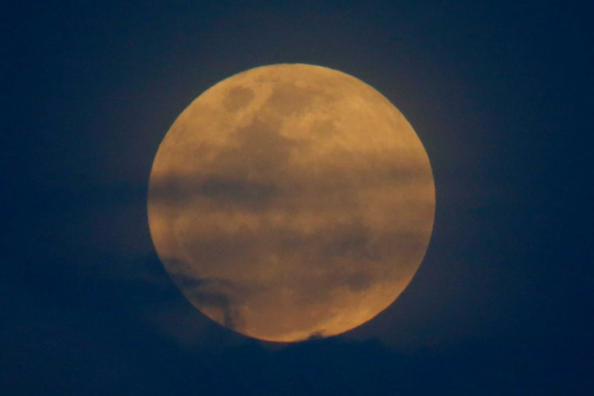 Close shot of the moon glowing orange and blue.