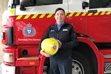 Tasmania Fire Service's first female Station Officer, Sandra Onn, stands in front of a fire truck.