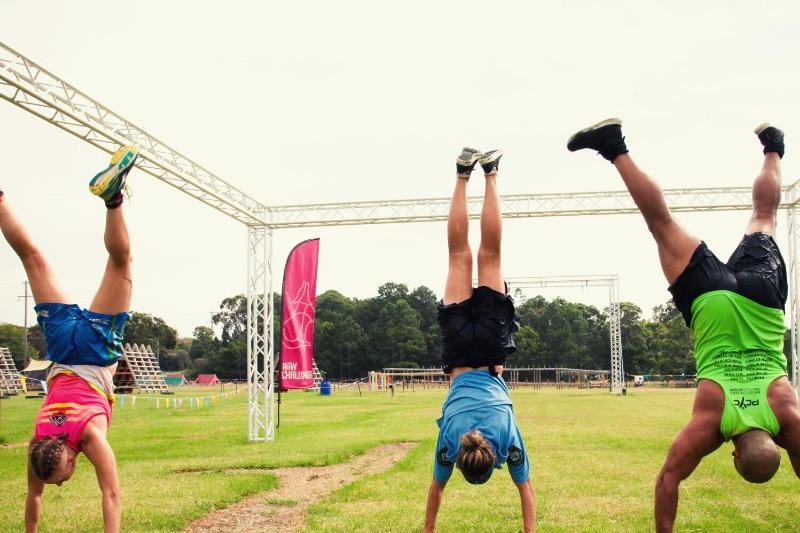 Three people doing handstands on grass wearing athletics clothes.