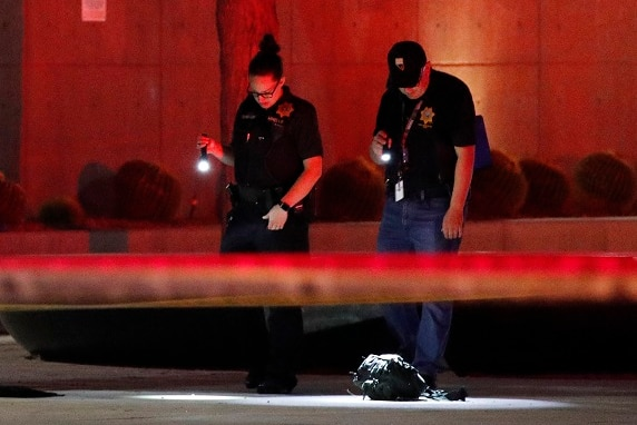Two police officers with flashlights look down at a crime scene flooded in red light.