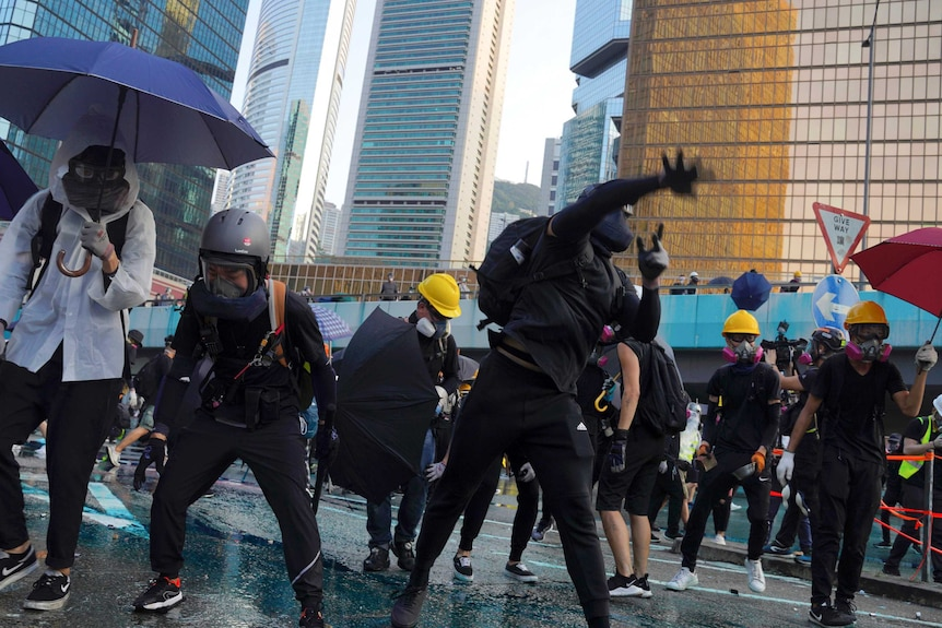 An anti-government protester throws a rock amid a large crowd