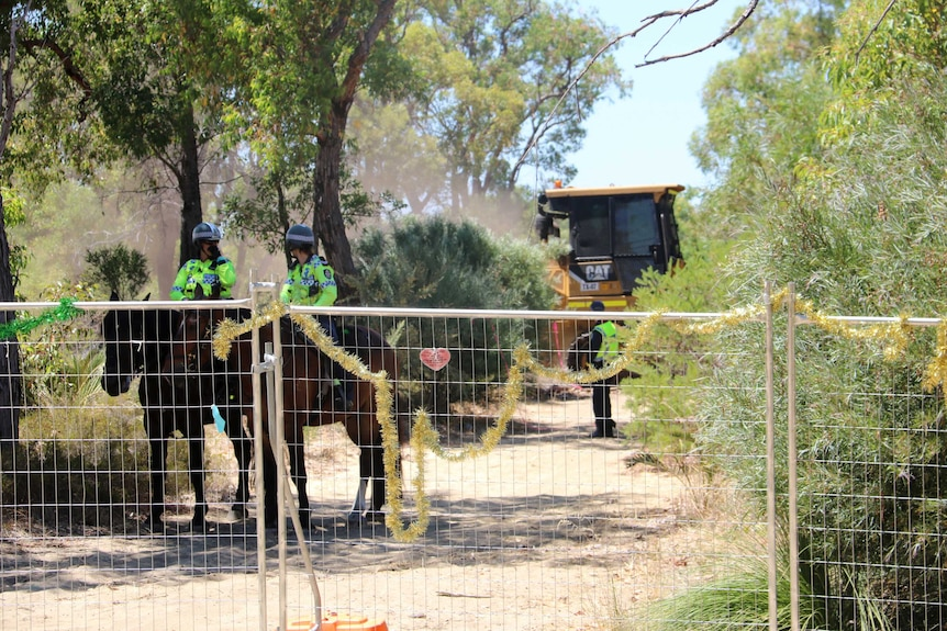 Machinery and police officers on horseback in bushland behind a fence.