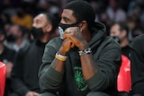 Kyrie Irving wearing a hoodie and a facemask.