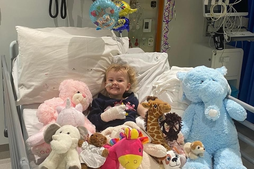Young girl lying in hospital bed surrounded by stuffed toys and balloons.