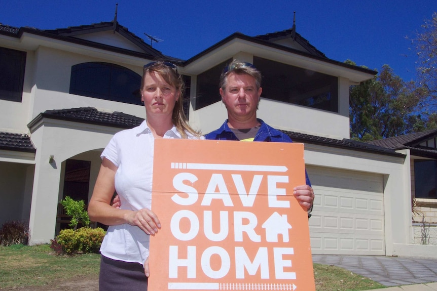 Tanya and Damon Smirk stand in front of their home holding a Save Our Home sign.