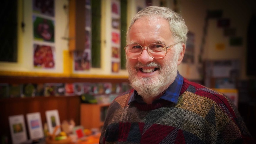 A grey-haired man in a colourful jumper smiles at the camera.