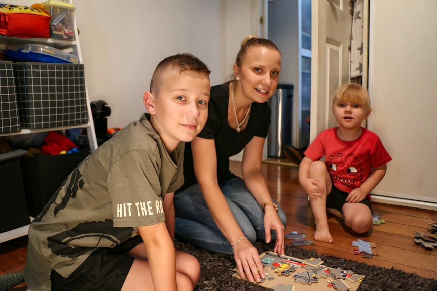The young family play on the ground in their home.