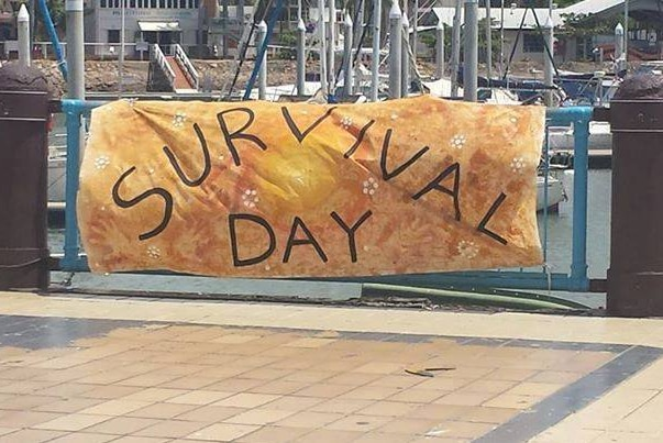 A banner with the words survival day written on it hangs on a fence on a sidewalk.