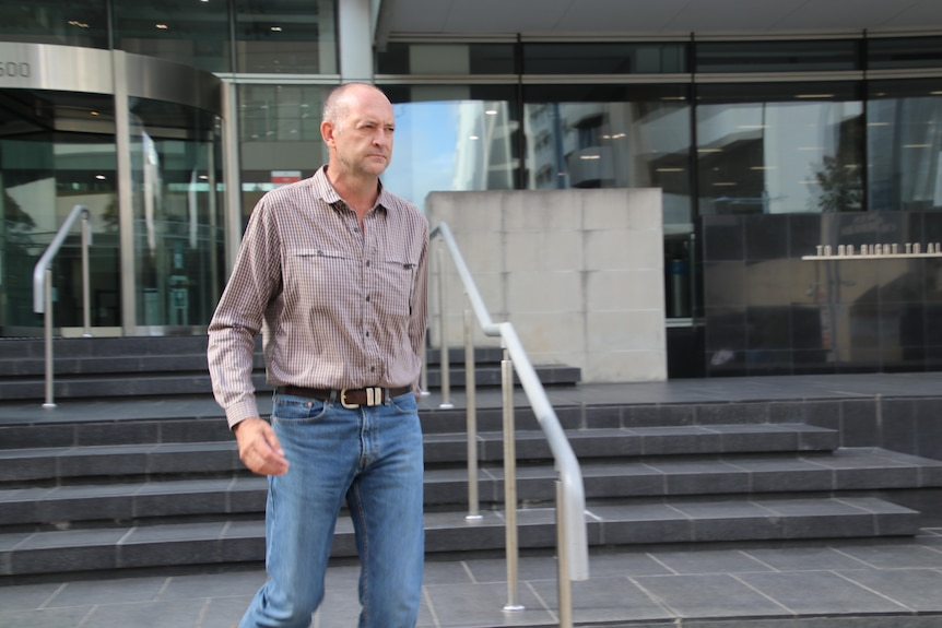A photo of a man wearing a mushroom-coloured shirt and jeans.