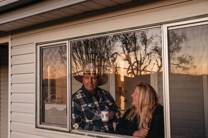 Greg and Lauren Newell looking out the window of their farm stay cottage.