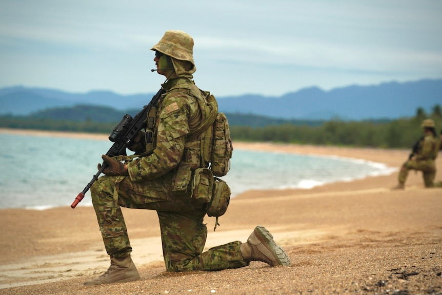 An infantry soldier in combat uniform keeps lookout on a beach in northern Queensland.
