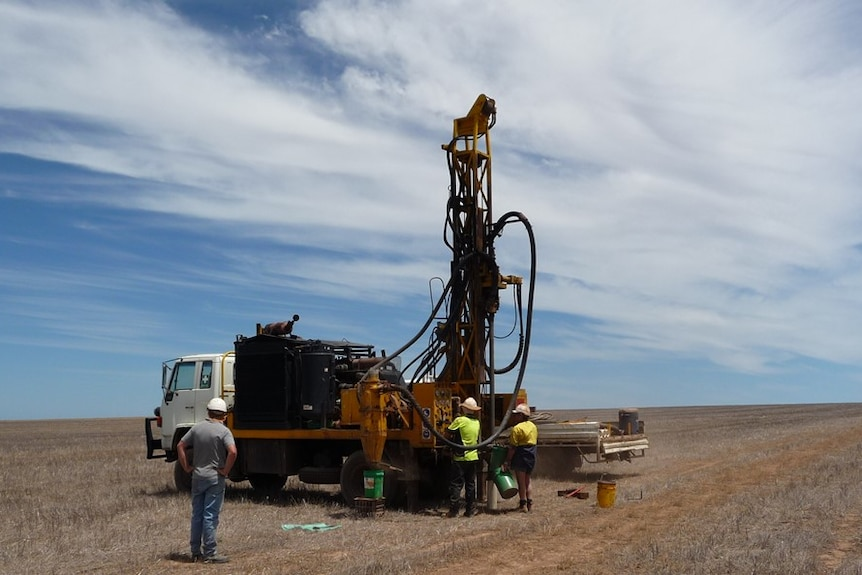 A drilling rig mounted on the back of a small truck sits in an empty field, three men are operating it.