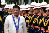 Philippine President Rodrigo Duterte walks past honour guards.