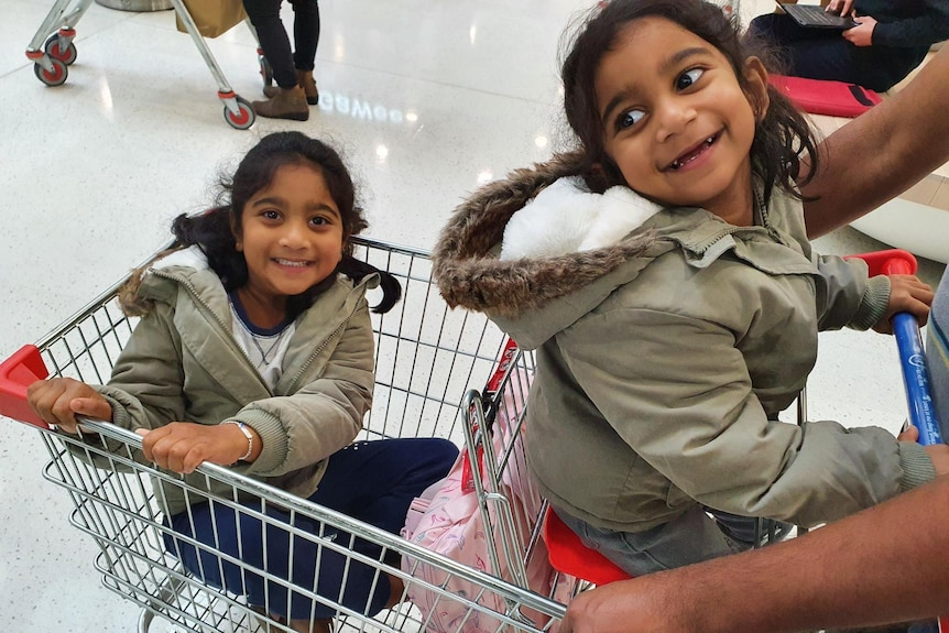 Kopika and Tharnicca sitting in a shopping trolley smiling at the camera.