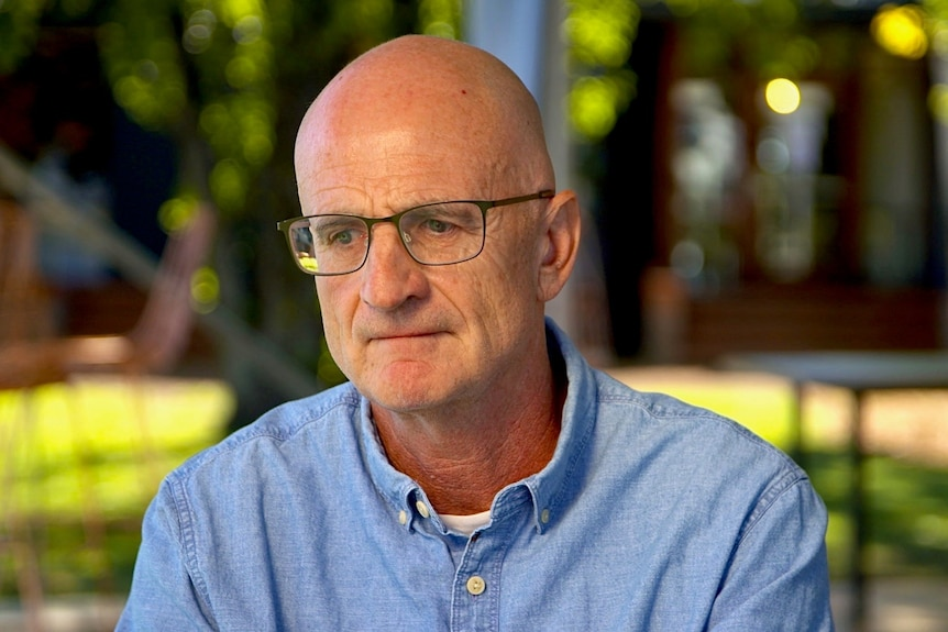A man wearing glasses and a blue shirt.