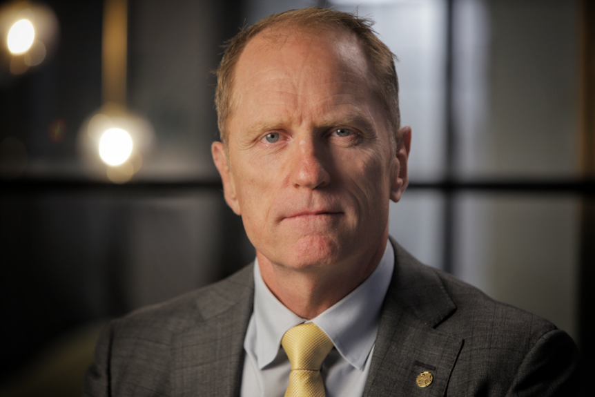 A blue-eyed, older pale man with receding red hair, wearing a grey suit jacket and shirt with a yellow tie.