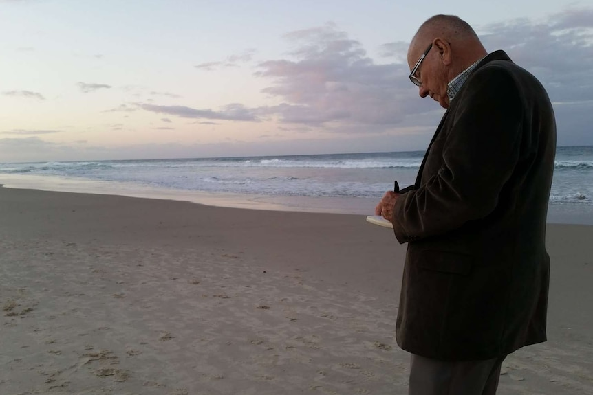 An older man, with pen and paper in hand, stands on a beach