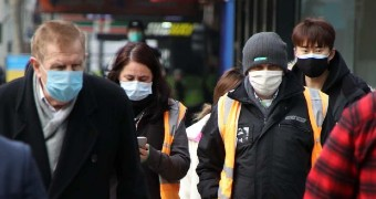 People walking down a Melbourne footpath wearing dark coats and face masks.