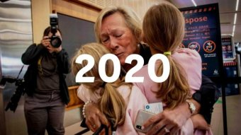 A woman hugs two young girls at an airport. Text saying 2020 is imposed on top
