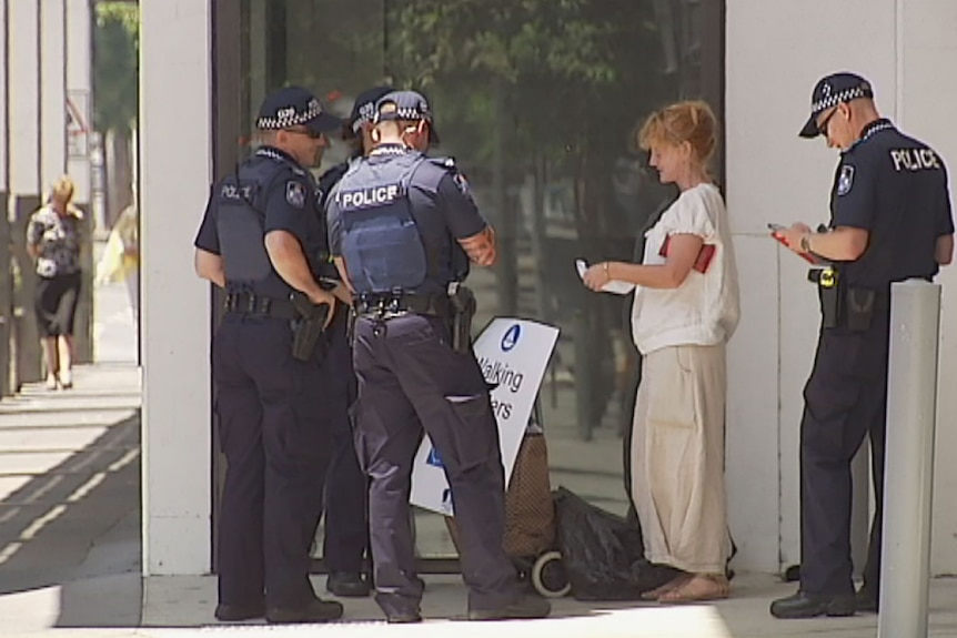 Police tell a lone protester outside the Brisbane Convention Centre to move on Saturday November 1 after the area became a restricted zone.