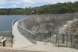 A large concrete dam wall with water on one side stretches into the distance