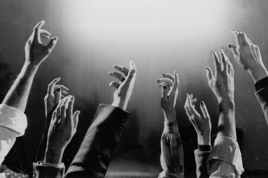 A black and white still from 1987 film Heaven with many arms reaching up