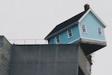 shot of blue weatherboard house teetering on the edge of a building