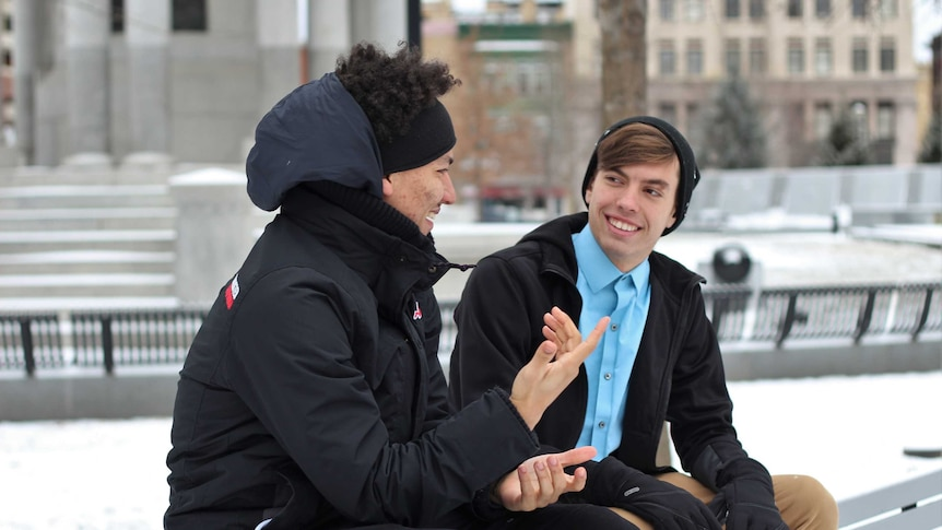 Two young men sit on park bench in conversation