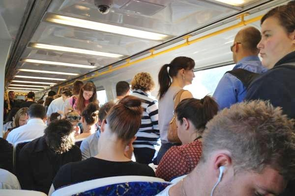 People sitting and standing inside a train carriage.