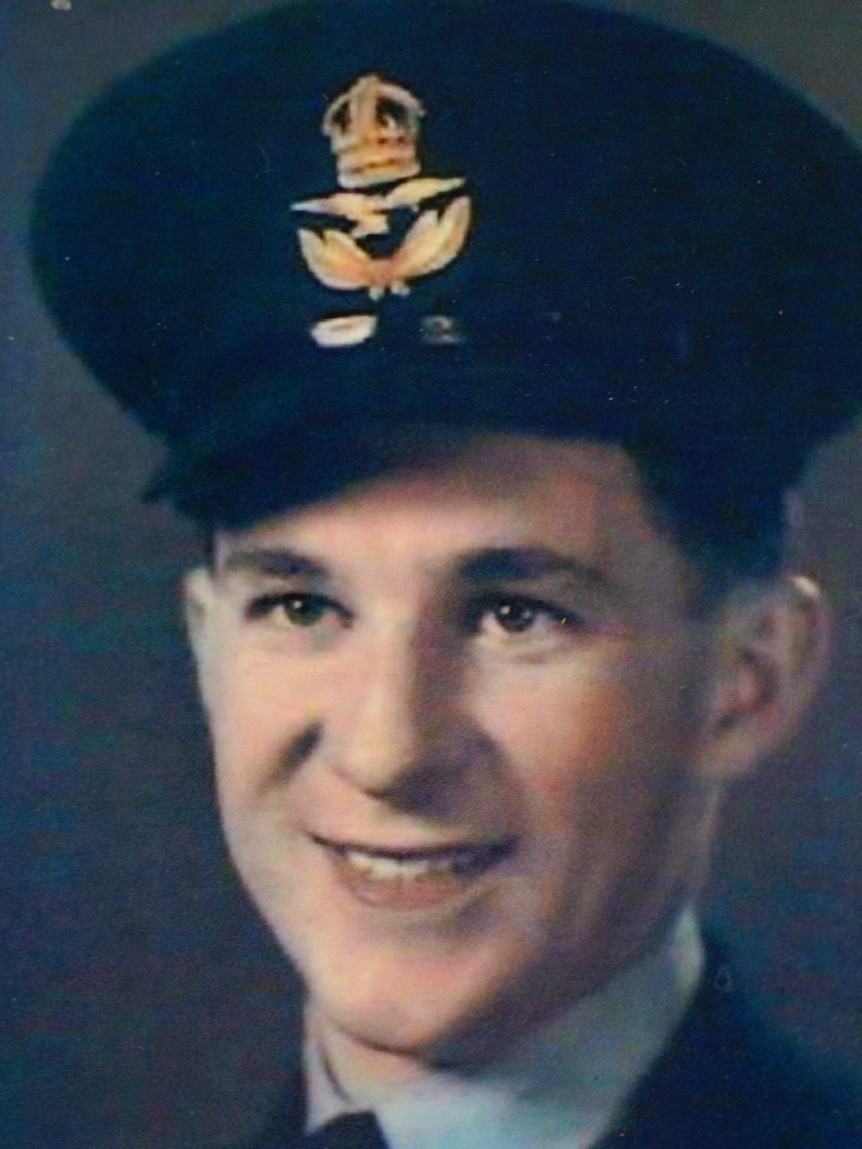 A headshot of a young smiling man in a military uniform.