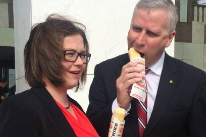 A man and a woman in suits eat Chiko Rolls.