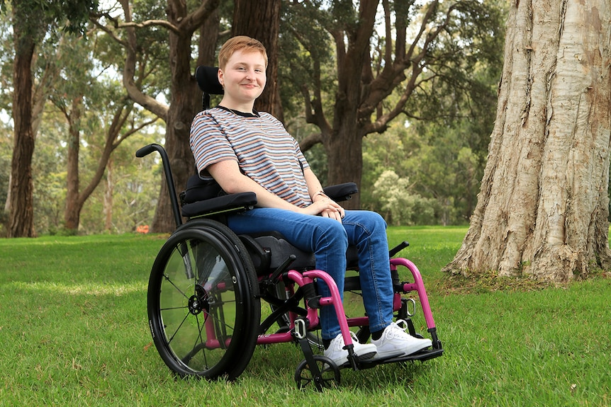 A young woman sits in her wheelchair. She wears a striped top, blue jeans and white runners and smiles.