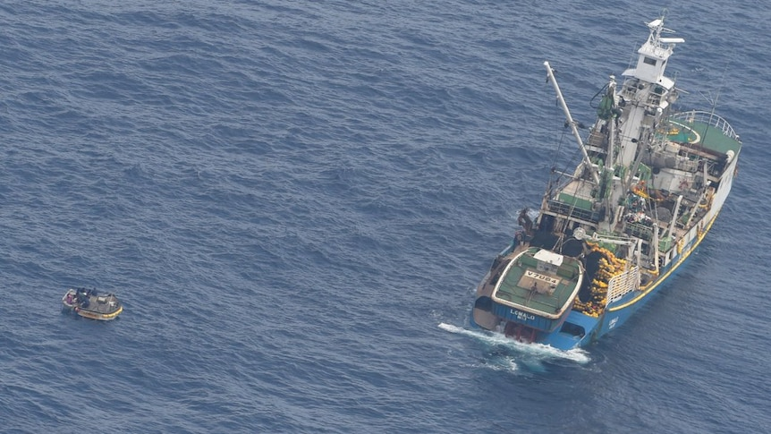 Aerial shot of fishing boat sitting along side small dinghy in the ocean.