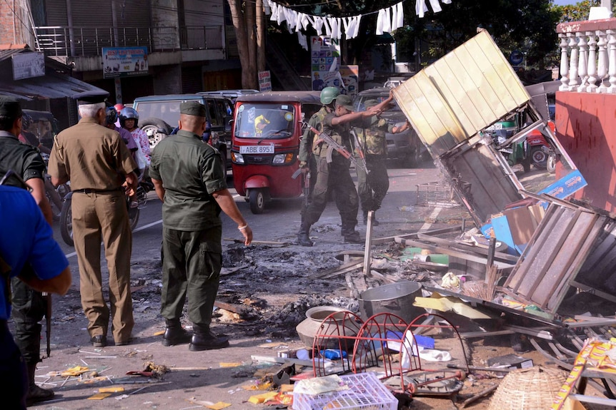 Sri Lanka's army soldiers remove the debris from a vandalized building