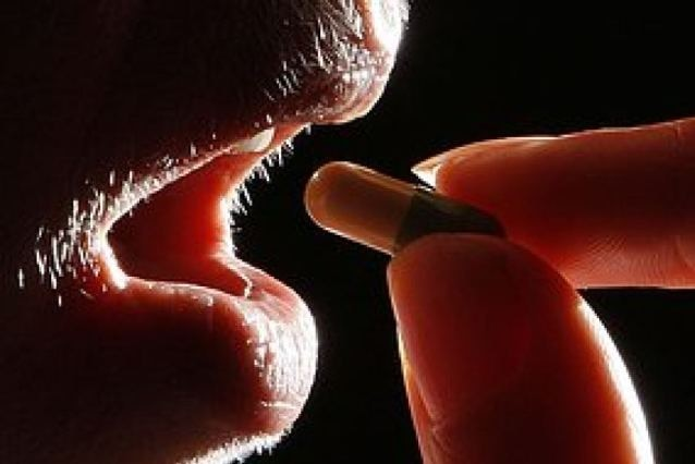 A person holds a pill up to their mouth.