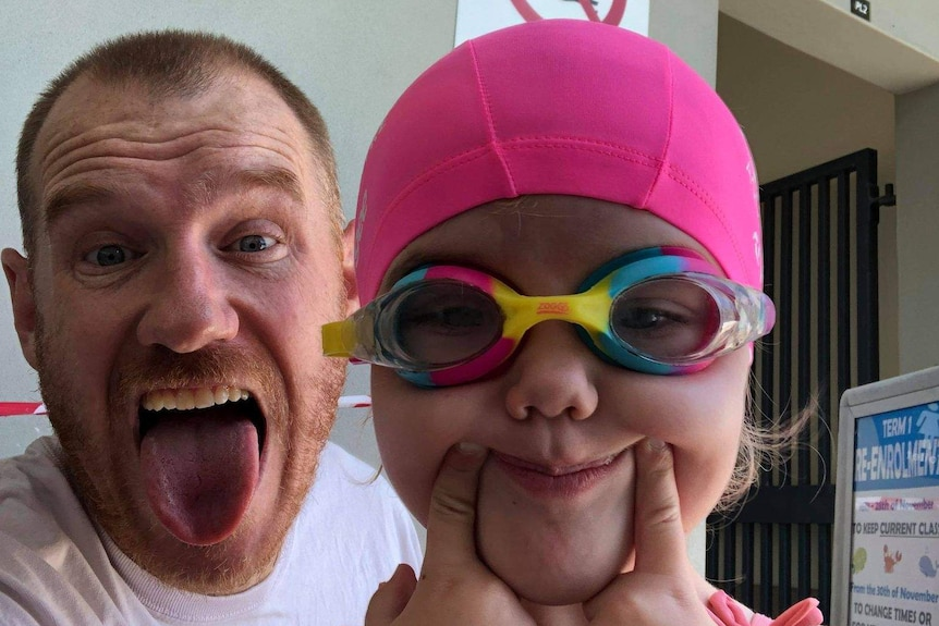A man sticks his tongue out and a little girl wearing a swimming cap and goggles makes a funny face.